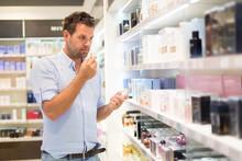 Elegant Man Choosing Perfume I...