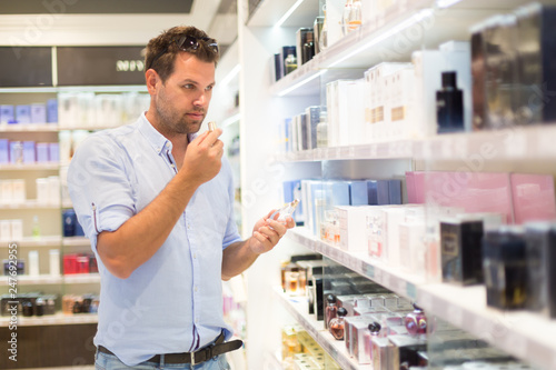 Fototapeta Elegant man choosing perfume in retail store. Casual man testing and buying gift for his lady in a beauty store. obraz