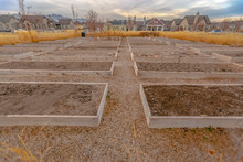 Row Of Raised Beds Against Homes And Sky In Utah