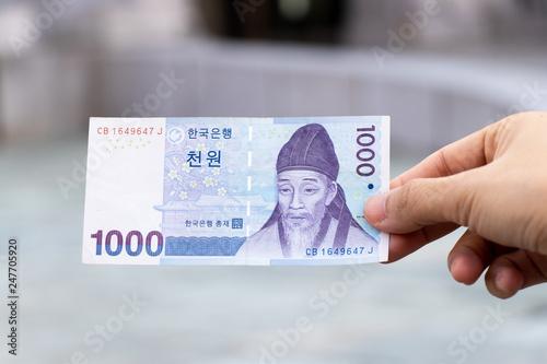 Fotomural  Man hold south korea banknote 1000 won on blurred background