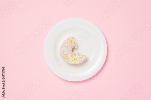 White plate with bitten off Fresh tasty sweet donut on a pink background Canvas Print
