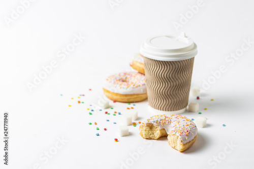 A paper cup with a lid, coffee or tea to go and fresh tasty donuts and sweet multicolored decorative candies on a white background Wallpaper Mural