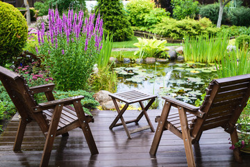 Two wooden chairs near the pond