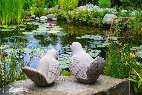 Papiers peints Jardin A couple of birds - garden sculpture against a pond