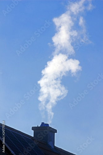 Stampa su Tela white smoke escaping from the chimney of a house