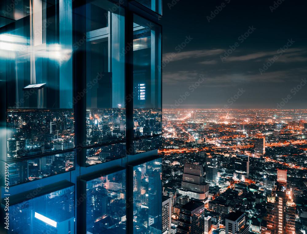 Fototapeta Glass window with glowing crowded city