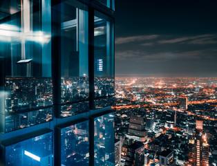 Glass window with glowing crowded city