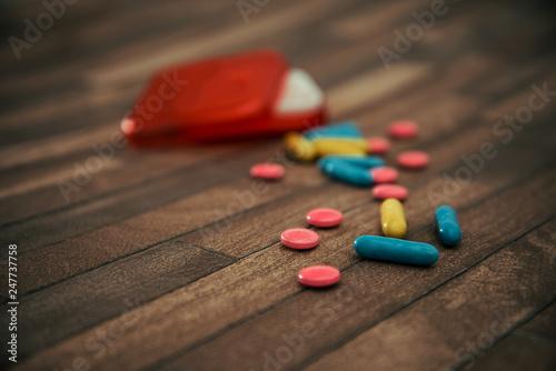 Fotografia  Medicine box and bottle on colorful pills