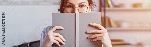 Photo  woman in glasses covering face with book