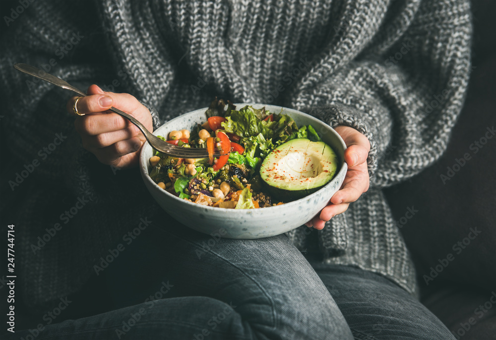 Fototapety, obrazy: Healthy vegetarian dinner. Woman in grey jeans and sweater eating fresh salad, avocado half, grains, beans, roasted vegetables from Buddha bowl. Superfood, clean eating, dieting food concept