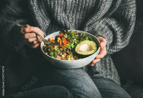 Fototapeta Healthy vegetarian dinner. Woman in grey jeans and sweater eating fresh salad, avocado half, grains, beans, roasted vegetables from Buddha bowl. Superfood, clean eating, dieting food concept obraz