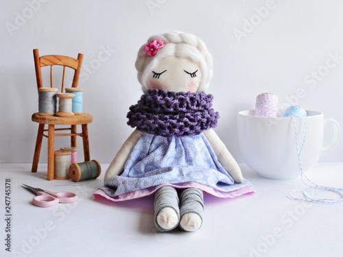 Fototapeta Handmade rag doll with white hair, wearing lovely dress and wool scarf