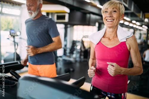 Staande foto Hoogte schaal Senior people running on a treadmill in health club.