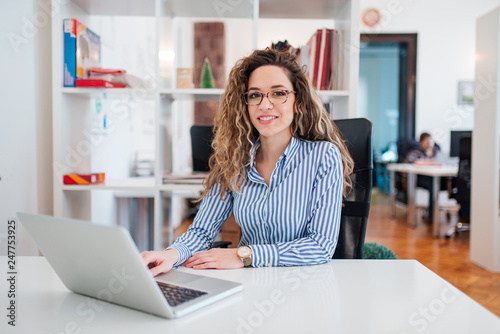 Portrait of confident young businesswoman in formal wear sitting at workplace, looking at camera Wallpaper Mural