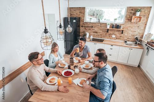 Fototapeta High angle image of five multi-ethnic friends or roommates eating homemade pancakes. obraz
