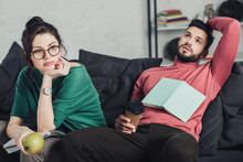 Bored Woman In Glasses Holding Apple And Sitting Near Handsome Man With Paper Cup