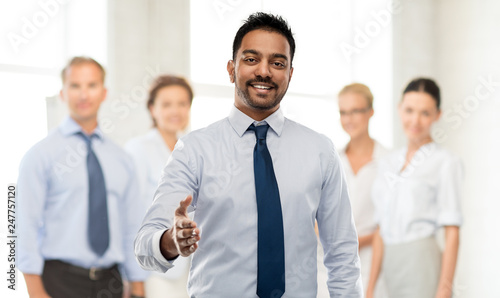 plakat business, office worker and people concept - smiling indian businessman stretching hand out for handshake over colleagues on background