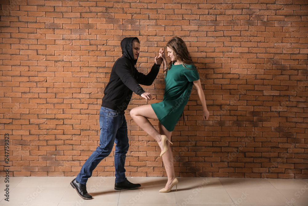 Fototapety, obrazy: Young woman defending herself from attack by thief against brick wall