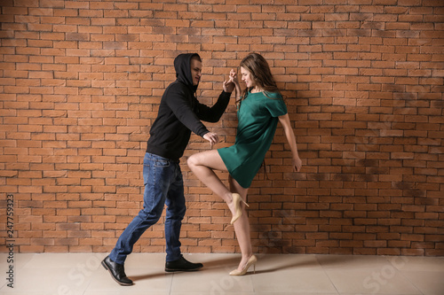 Fotografiet  Young woman defending herself from attack by thief against brick wall