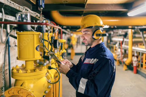 Young Caucasian worker in protective suit using tablet while checking machines in heating plant фототапет