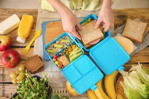Valokuvatapetti Mother preparing lunch for schoolchild at table