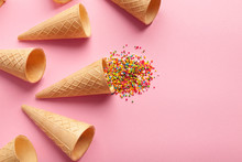 Empty Ice-cream Waffle Cones And Colorful Sprinkles On Pink Background,