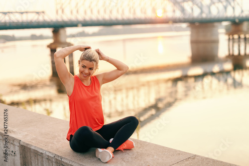 Fotografía  Pretty smiling blonde Caucasian woman in sportswear with legs crossed binding her hair while sitting on the wall