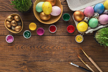 Painted Easter Eggs And Brushes On Wooden Table