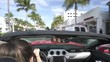 Backseat view of woman driving red convertible car in sunny Miami beach
