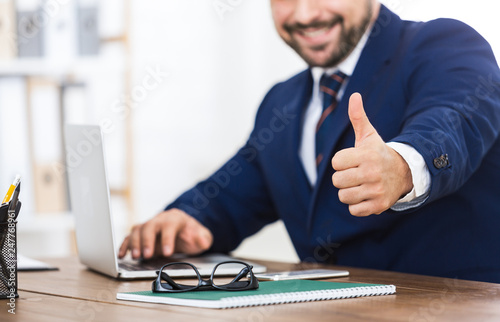 Fotografía  Successful businessman showing thumb up at workplace