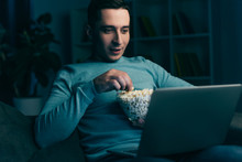 Handsome Man Watching Movie On Laptop And Holding Bowl With Popcorn At Home