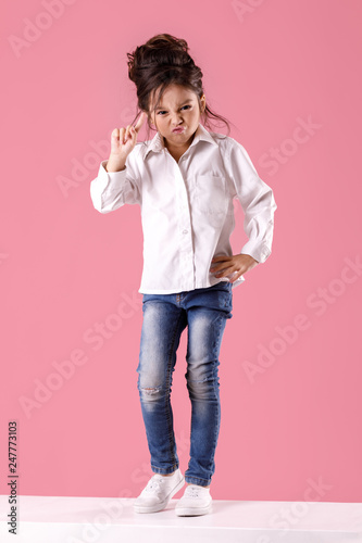 Fényképezés  angry little child girl in white shirt with hairstyle looking to camera on pink background