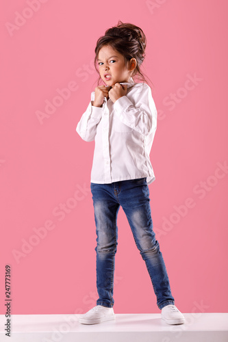 Valokuvatapetti Full length portrait of angry screaming little child girl in white shirt with hairstyle looking to camera on pink background