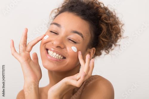 Fotografía Portrait of laughing woman applying face cream