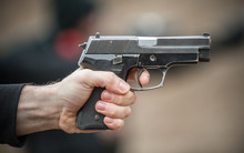 Left Hand Shooter Shooting And Holding Gun. Close-up Detail View