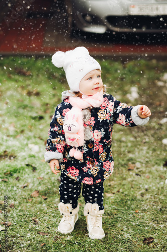 Portrait of sweet girl gesturing by hands, playing and walking at garden in winter season Wallpaper Mural