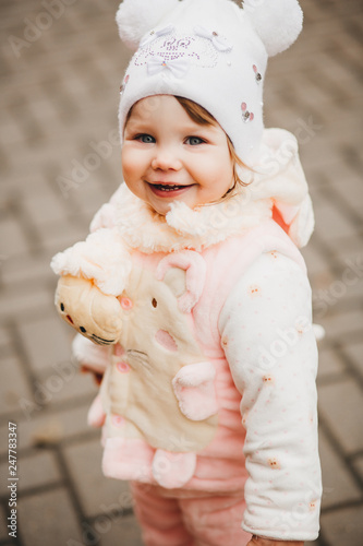 Portrait of happy smiling little girl wearing in white hat like mikey mouse walking in yard and playing, looking and turned at camera Wallpaper Mural