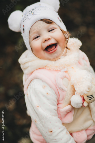Photo  Positive smiling little girl looking  and turned at camera and laughing