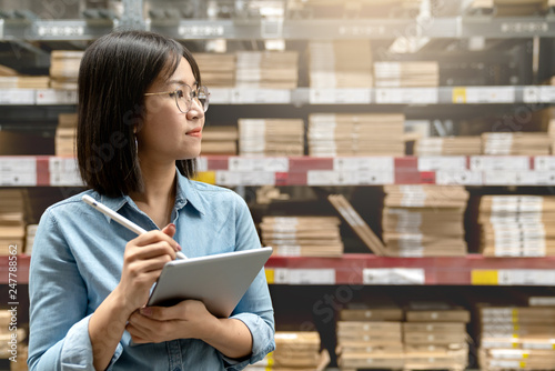 Fotografía  Young attractive asian worker, owner, manager, entrepreneur woman holding smart tablet computer with efulfillment service business warehouse management stock online concept