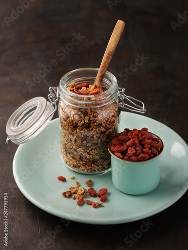 Poster Coffee bar Homemade granola , muesli in open glass jar with goji berries and fresh bee pollen on dark background with copy space.