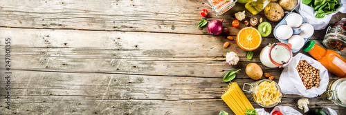 Fototapeta Zero waste shopping and sustanable lifestyle concept, various farm organic vegetables, grains, pasta, eggs and fruits in reusable packaging supermarket bags. copy space top view, banner obraz