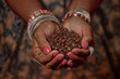 canvas print picture - Brown feminine hands in traditional jewelery hold a handful of coffee beans