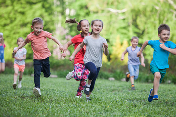 A group of happy children of boys and girls run in the Park on the grass on a...