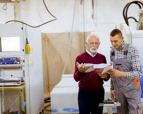Valokuva  Men standing and discuss in furniture factory, one of them is disabled person