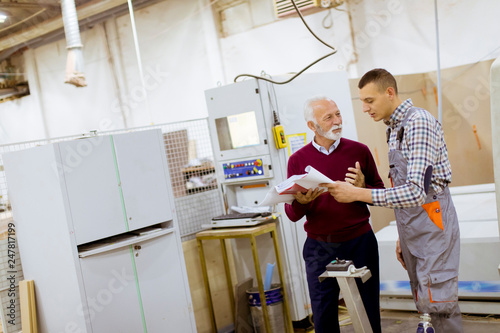 Obraz na plátne Men standing and discuss in furniture factory, one of them is disabled person