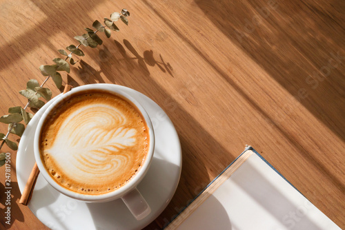 A Cup of hot latte art coffee on wooden table with book in coffee shop cafe Tableau sur Toile