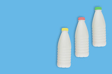 Fresh Dairy Product In Three Full Plastic Bottles For Milk, Kefir Or Yoghurt With Red And Yellow And Green Caps On Blue Table On Kitchen. Copy Space For Your Text. Top View. Cooking Concept