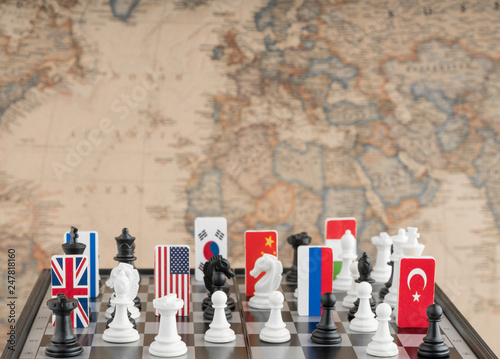 Foto Country flag symbols on the chessboard with figures on the background of the political map of the world