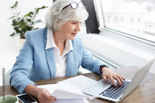 Obraz Reputable 65 year old female executive in stylish bkue suit enjoying wireless high speed internet connection while using laptop, analyzing accounts, holding papers in her hand, looking at screen - fototapety do salonu