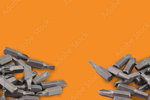 Fotografie, Obraz  Two heaps of different interchangeable heads or bits for manual screwdriver for woodworking and metalworking on orange background with copy space for your text